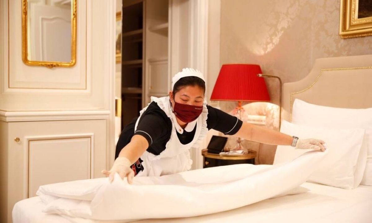 88283098 a cleaning lady wearing a protective face mask prepares a bed in a suite at the traditional