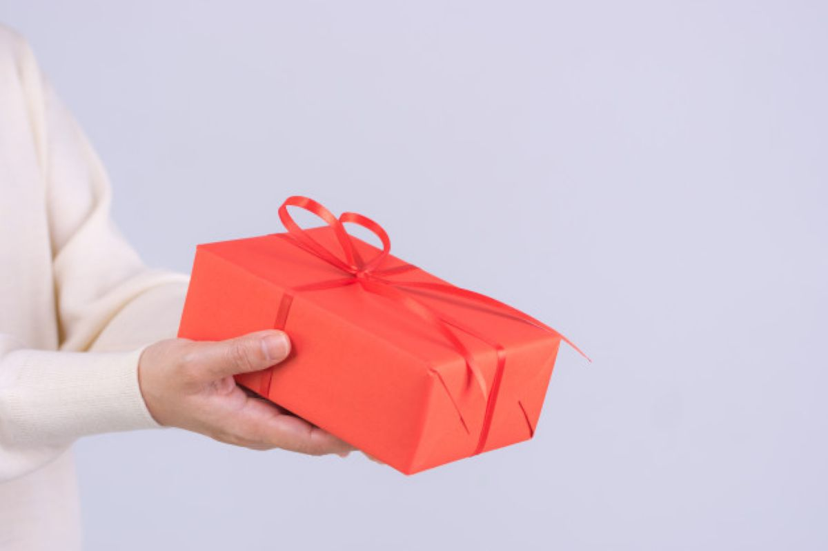 closeup hands giving gift box woman deliveries a red package gift with red ribbon birthday boxing day or christmas concept 101840 413