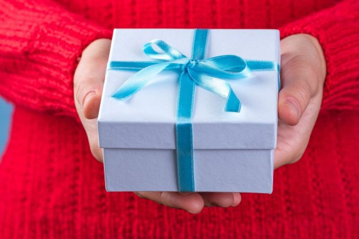 female hands holding a small white gift box wrapped with blue ribbon to give and receive gifts 122732 157